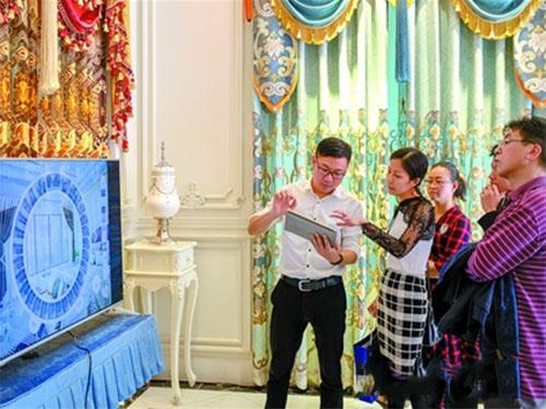 """路易·美邦国际布艺软装馆内,销售人员介绍针对家纺布艺行业开发的""""布糖""""应用软件"""