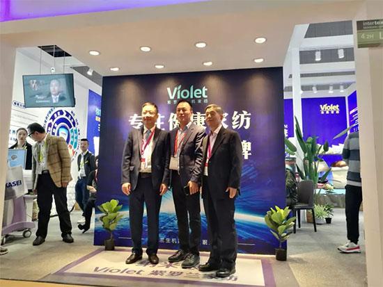 中国家纺协会原会长杨东辉、现任会长杨兆华与董事长陈永兵在紫罗兰展位上合影