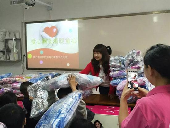 明超家纺的刘桂玉女士正在给孩子们发放床品