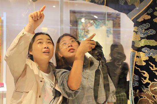采访团的记者欣赏展馆内的纺织品