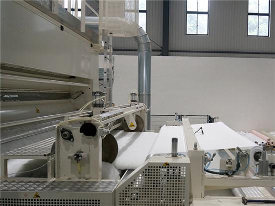 自动化机器将棉絮均匀平铺在被罩内