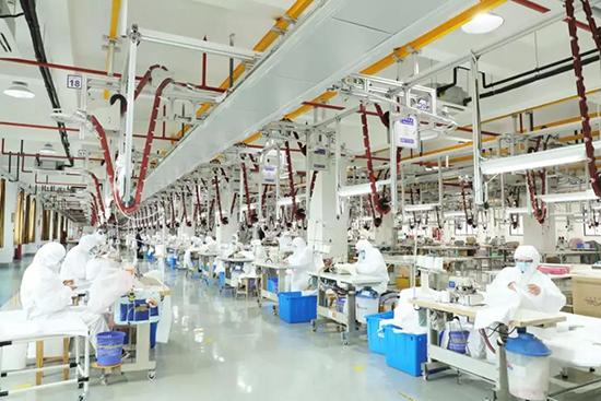 员工穿戴好防护服、口罩等防护用品在一线生产
