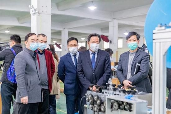 浙江金蝉布艺股份有限公司董事长杨来荣向领导们介绍口罩生产线